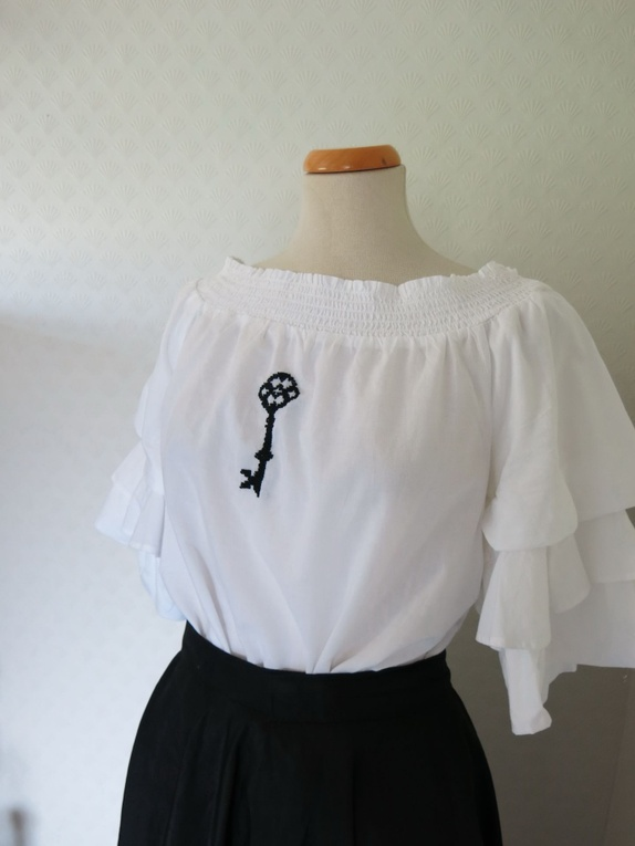 f1dfdd3a Hvit bluse i off-shoulder modell med håndbroderi laget av meg. Broderiet er  en nøkkel i antikk stil brodert med svart garn. Blusen har rysjer på ermene  og ...