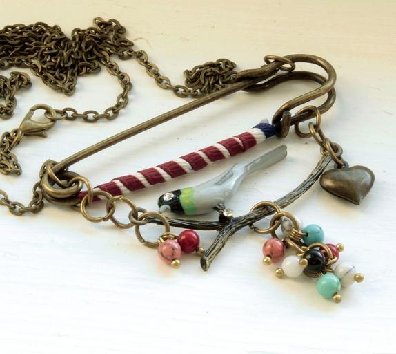 Smykke med sikkerhetsnål, fugl mm - Norge - Artig smykke med sikkerhetsnål i matt antikk Bronse. Liten fugl og små perler i forskjellige halvedelstein perler. Lengde på kjedet er 60 cm. SØKEORD: Rød, blå, grå, hvit, blå, fugl, fugler, sikkerhetsnål, LS smykker, epla.no - Norge