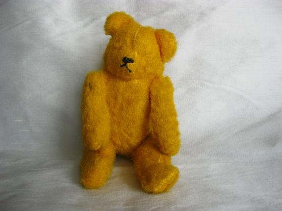 Liten teddybjørn - vintage - Norge - Liten gul gammel bamse, fra 1950-tallet. Bare 17-18 cm høy. Hard innmat, bevegelige armer og bein.Litt skjev og skakk, ett bein er kortere ut enn det andre... Har ikke øyne, de har kanskje falt av? - Norge