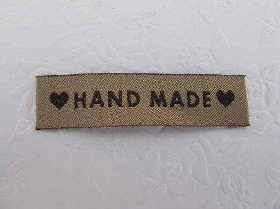 Handmade merkelapp - Norge - Handmade merkelapp Merkelapp i vevd materiale med beige bunn og brune bokstaver med påskriften: Handmade. Supre til å sy på dine strikke, hekle eller syprosjekter. De er 6 cm x 1,5 cmPrisen er pr stk - Norge