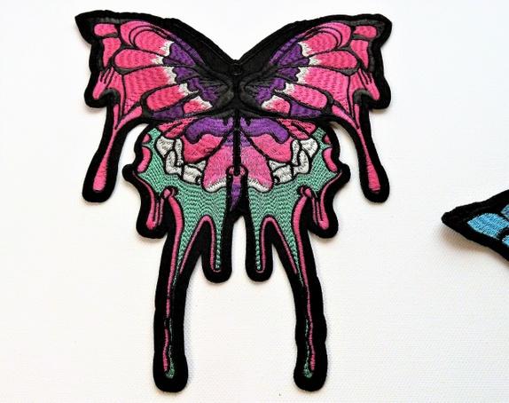 STOR (23 x 27 cm) Rosa/Lilla Sommerfugl - Applikasjon (6293) - Norge - Art: 6293. Stor, flott og forseggjort sommerfugl rosa, lilla, sort, hvitt og grønt. Litt solid, god og fast i fasongen, til dekorasjon av klær, eller interiør.Måler ca: 23 x 27 cm OBS! Dette er ikke et strykemerke, det må limes eller sys på. - Norge