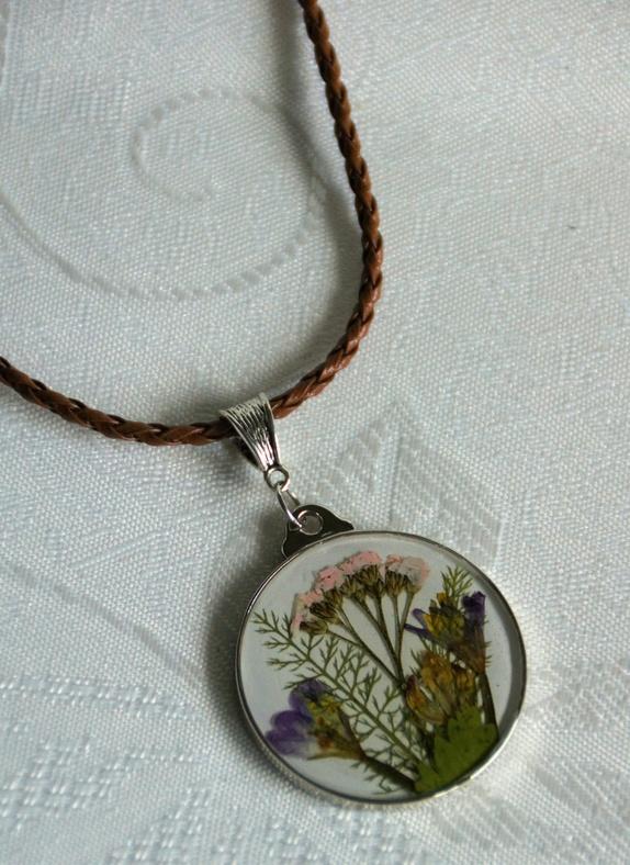 Ville blomster i epoxy - Norge - Brun skinnsnor med rund anheng, håndplukket og tørket ville gres og blomster støpt i epoxy. Lengde er 63 cm +5 cm ekstra kjede. Anheng er 4 cm i diameter. Kun ett eksemplar. - Norge