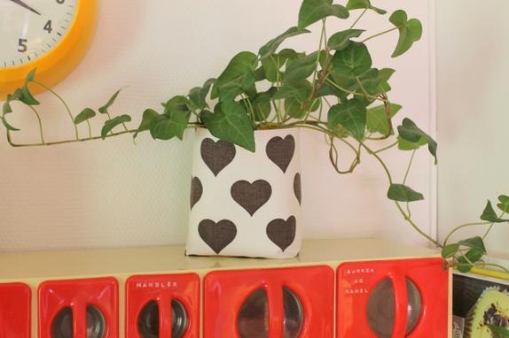 Søt plantepose - Norge - Denne planteposen er sydd av en søt retrogardin i hvit med brune hjerter. Innsiden er gul voksduk som er kjøpt ny. Vliselin er strøket på mellom lagene for å få en stivere pose. Mål 14 cm høy, 38 cm rundt posen Siden voksduken ikke skal va - Norge