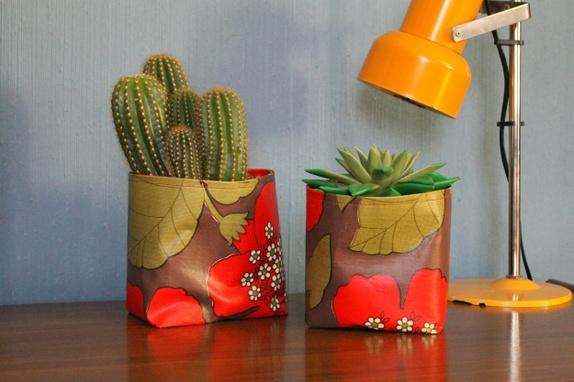 To retro planteposer i voksduk - Norge - Sett med to planteposer sydd av en retro brun voksduk med grønne blader og herlige blomster i rødt. Innsiden er rød voksduk som er funnet på brukthandel. Vliselin er strøket på mellom lagene for å få stivere poser. Rengjøres enkelt med fu - Norge