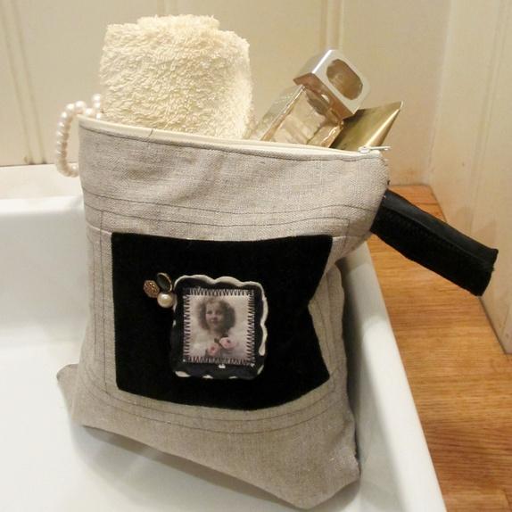 FineLines toalettmappe - Norge - Denne er sydd i lin med rutete stoff som fôr med tynn vatt, som gjør den litt stødigere, men på ingen måte stiv. Pynten er gammel sort fløyel med et lite jentebilde og tre gamle knapper påsydd. Relativt forseggjort, om jeg skal si det selv. - Norge