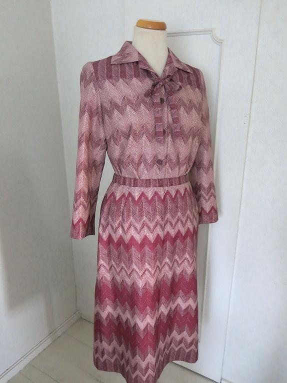 71696591 Vintage sett i mørkerøde/rosa toner som består av skjørt og bluse. Blusen  har belte i samme stoff. Skjørtet har glidelås og knapp i siden i tillegg  til ...