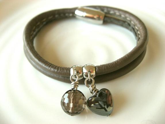 Str M. Røykkvarts og hematitt - Norge - Flott armbånd i gråbrunt lammeskinn. Lammeskinnet er mykt og veldig behagelig å ha på.Det har cremehvite stikninger, noe som gir armbåndet et tøft preg.Armbåndet går to ganger rundt håndleddet. Det lukkes med en magnetlås i rustfritt st