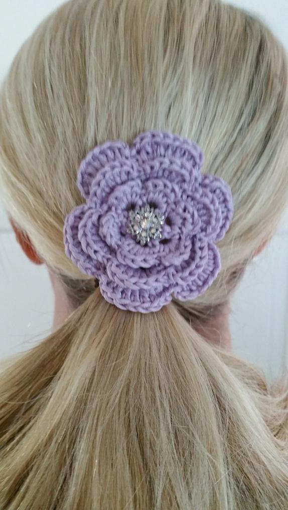 Hårnål, lyslilla - Norge - Lyslilla hårnål.Blomsten har en diameter på 7 cm.Det er festen en krystallknapp i midten av blomsten og en hårnål er festet på baksiden. Heklet med bomullsgarn.Dekorative i håret eller hvis du fjerner hårnålen kan blomstene være fin bord - Norge