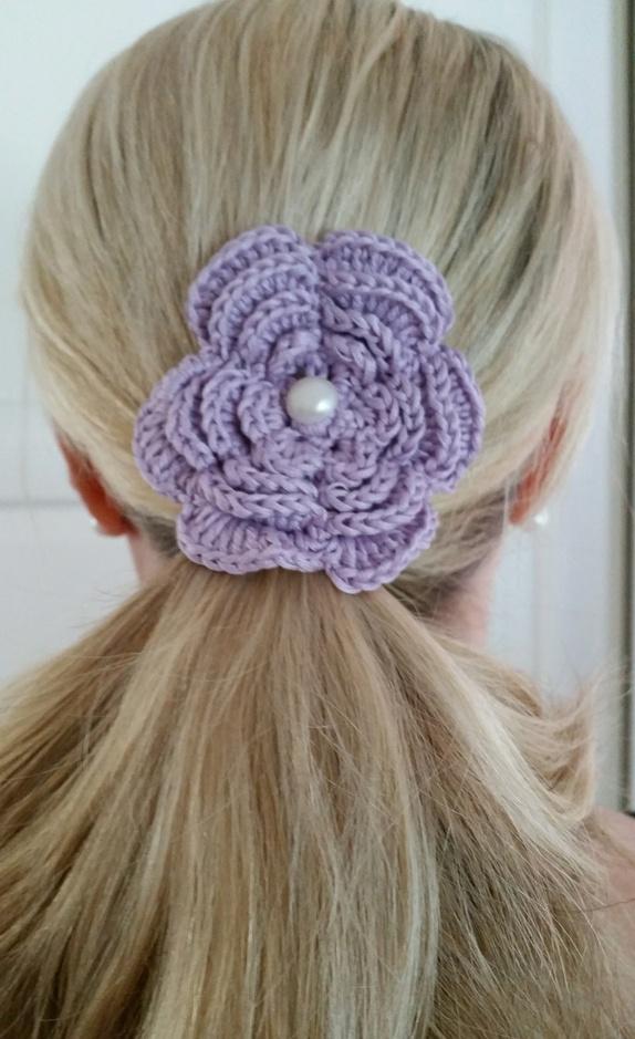 Hårnål, lyslilla - Norge - Lyslilla hårnål.Blomsten har en diameter på 8 cm.Det er festen en perleknapp i midten av blomsten og en hårnål er festet på baksiden. Heklet med bomullsgarn.Dekorative i håret eller hvis du fjerner hårnålen kan blomstene være fin bordpyn - Norge