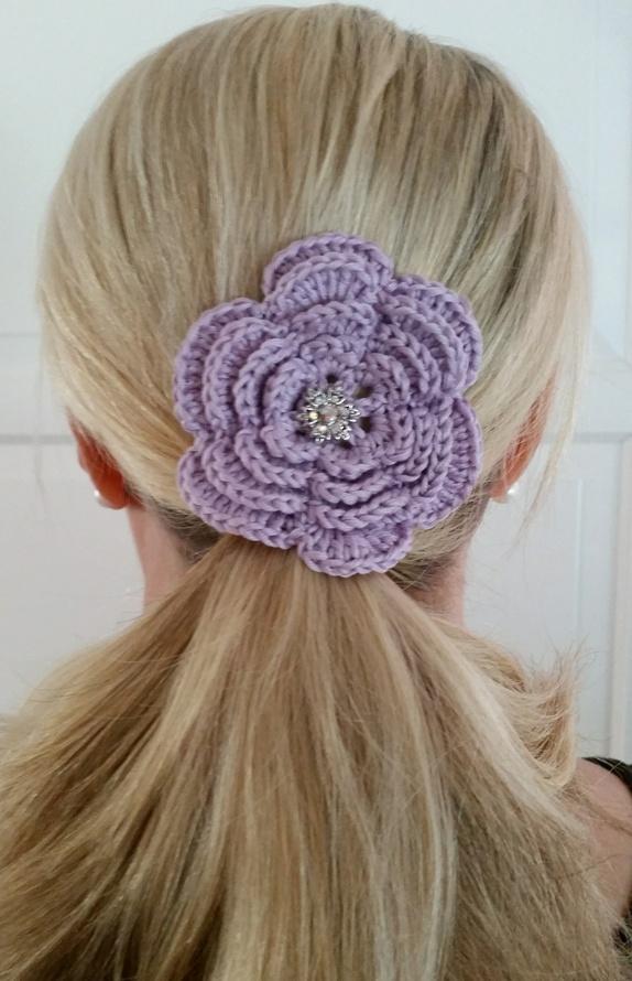 Hårnål, lyslilla - Norge - Lyslilla hårnål.Blomsten har en diameter på 8 cm.Det er festen en krystallknapp i midten av blomsten og en hårnål er festet på baksiden. Heklet med bomullsgarn.Dekorative i håret eller hvis du fjerner hårnålen kan blomstene være fin bord - Norge
