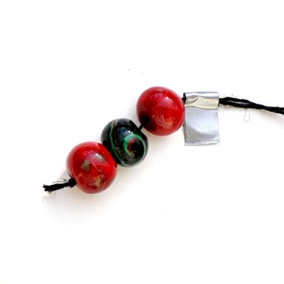 3 røde/sorte håndlagde perler - Norge - Håndlagde perler i rødt og sort og litt grønt - ca 15-16mm. Nydelig sett. Lampworkperler er unike kunstperler som aldri blir identiske. De smeltes av glasstenger med spesialutstyr og en perle kan ta mellom 5 minutter og en time å lage.Trollsme - Norge