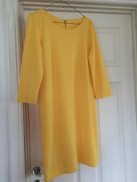 89506196 Fantastisk frisk kjole i med trekvart lang arm i solgul farge.Rund  halsåpning og glidelåsåpning bak. Kjolen ser ikke ut til å ha vært i bruk.