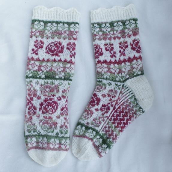 40dea59ca31 Sokkene er strikket i ull med forsterking i garnet. Det er en liten  blondekant over vrangborden og de har mønster ...