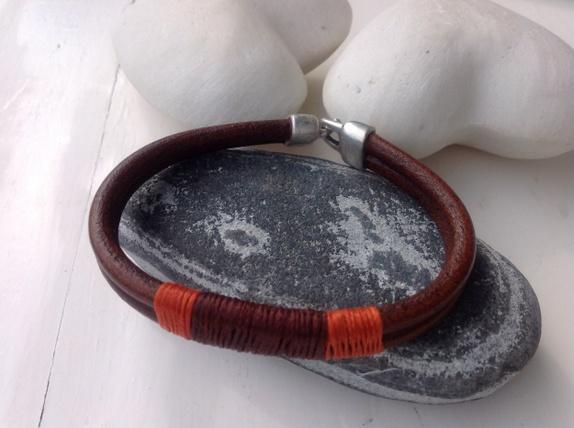Herre-skinnarmbånd - Norge - Dobbel,kraftig,brun skinnreim er dekorert med voksa bomullstråd i brunt og oransje. Solid,grei lås. Omkr. er ca. 21cm - Norge