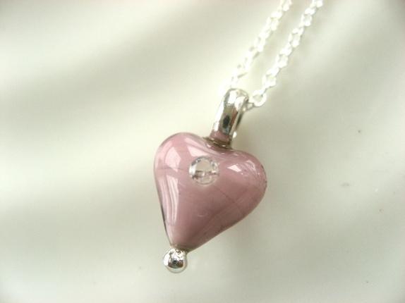 Sølv og glass, rosalilla hjertesmykke - Norge - Hjertesmykke i glass og sølv Fint, lite, rosa (mot lilla) glasshjerte med zirkonia,Høyden på selve hjertet er 10 mm.Sterling sølv, stemplet 925s.Leveres med et kjede som er 42 cm. Dette passer til barn eller som halsgropsmykke til voksen. Gi b - Norge